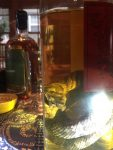 Bottle Of Pit Viper Whiskey with close up of open mouthed viper